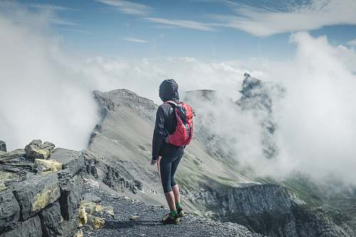 people man wearing black hooded jacket and backpack standing on rocks facing clouds person