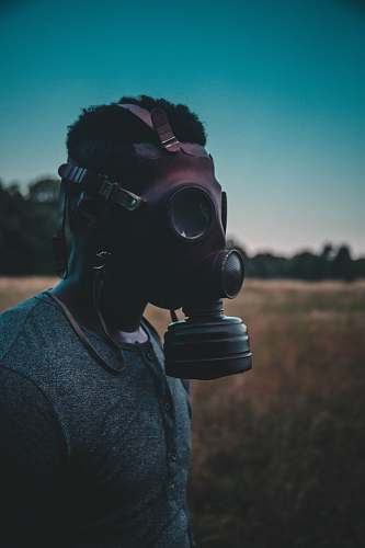 people man wearing brown gas mask standing on brown field person