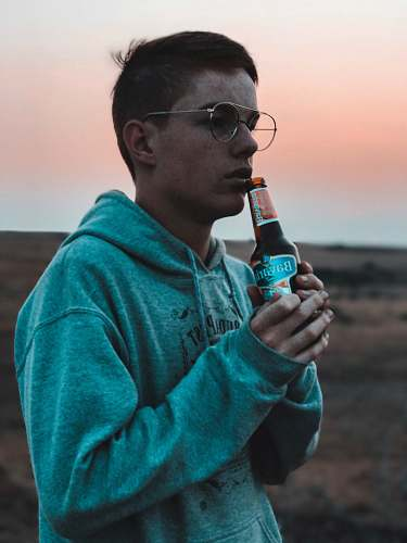 people man wearing hoodie holding a bottle of beer person