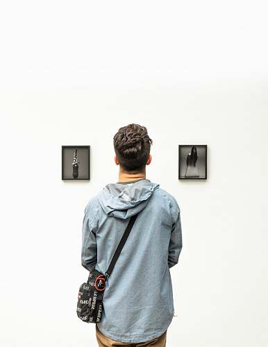 people man wearing hoodie looking at artworks person