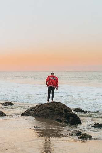 person man wearing orange jacket standing on seashore rock near beach people