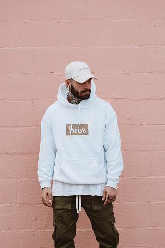 people man wearing white pullover hoodie standing against the wall person