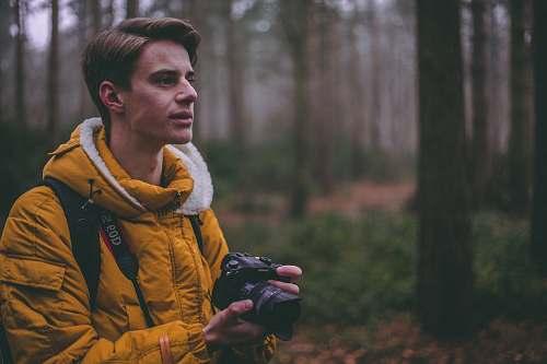 person man wearing yellow parka jacket holding DSLR camera photographer