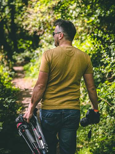 people man wearing yellow T-shirt holding tripod and DSLR camera person