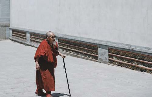 people monk walking while holding cane near white wall person