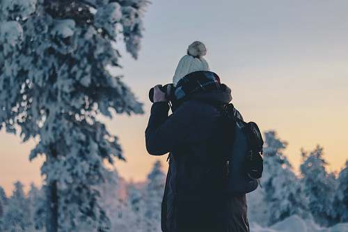 people person in black winter jacket holding black DSLR camera during daytime person