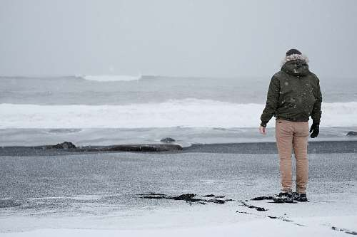 people person in grey jacket and brown standing standing at the shore person