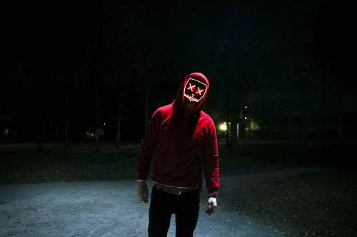 people person in red pullover hooded jacket standing in street during nighttime person