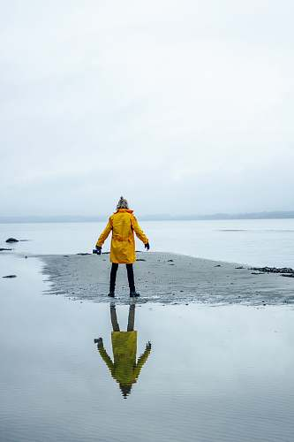 people person in yellow coat on gray sand surrounded by water person
