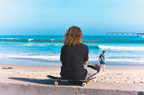 people person sitting on skateboard with sea shore background person