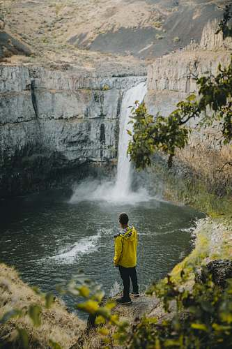 people person standing near waterfall during daytime person