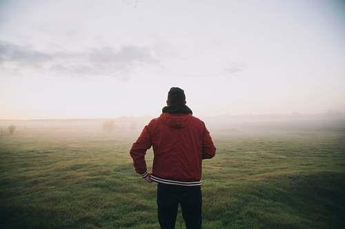 people photo of man wearing red jacket facing horizon person