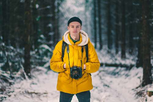 people selective focus photo of man standing holding DSLR camera person