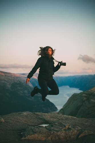 people selective focus photo of woman jumping holding camera person