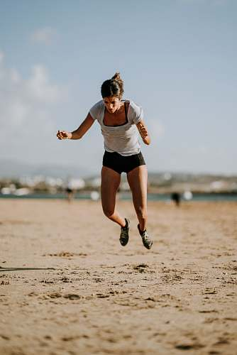 people selective focus photo of woman jumping on seashore person