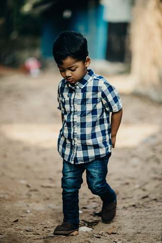 people selective focus photography of boy in blue and white checked button-up shirt looking down person