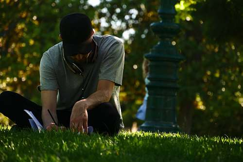 people selective focus photography of man sitting on grass and writing on notebook during daytime person