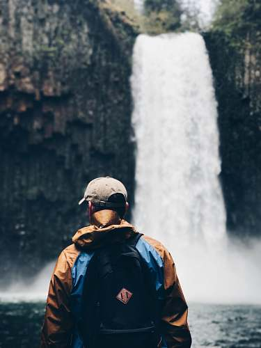 people selective focus photography of man standing on waterfalls person
