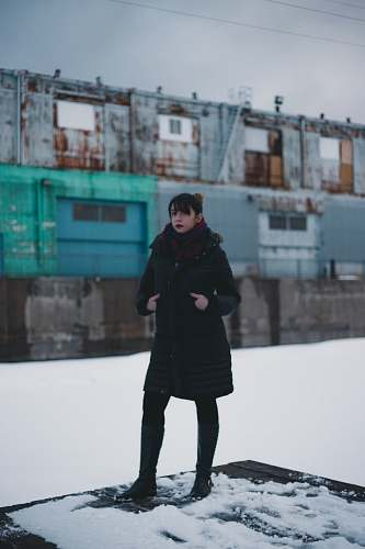people selective focus photography of woman wearing overcoat standing on intermodal container person