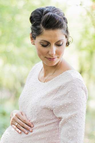 people selective focus photography pregnant woman looking down white holding her tummy person