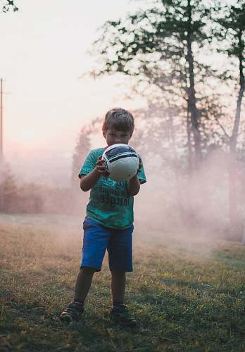 people shallow focus photography of boy holding a ball person