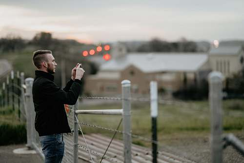 person shallow focus photography of man taking a photo near fences people