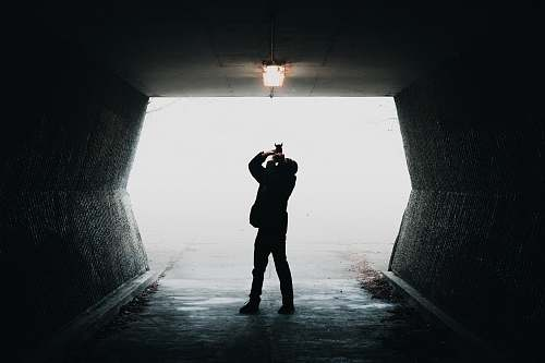 people silhouette of man taking photo of light inside tunnel way person