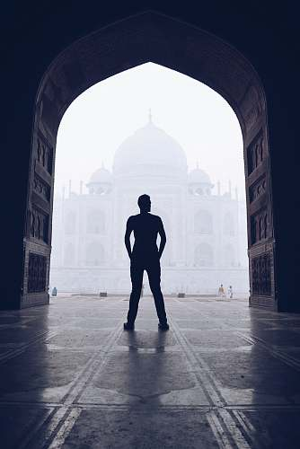 person silhouette photography of man standing near door in front of mosque people