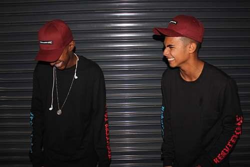 people smiling two men standing front of door shutter person
