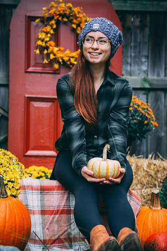 people smiling woman sitting and holding orange pumpkin person