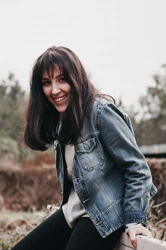 people smiling woman wearing blue chambray jacket person