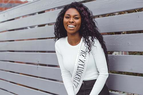 person smiling woman wearing Ms. National U.S. sash leaning on pallet wall people