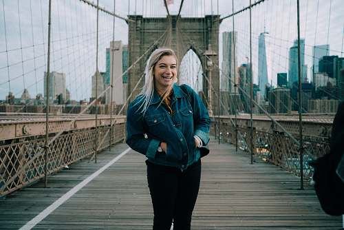 people standing smiling woman wearing blue denim button-up jacket at Brooklyn Bridge person