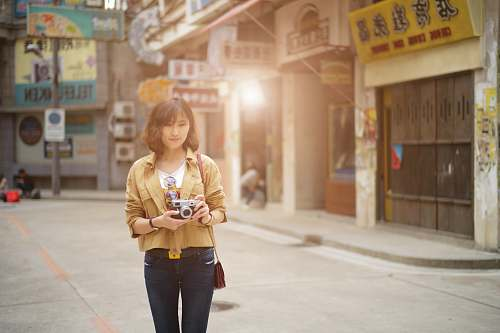 people standing woman holding camera near stores person
