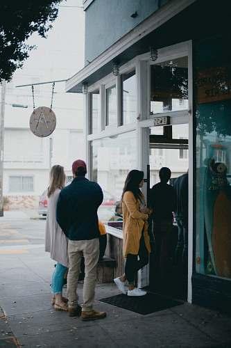 people three people standing near glass door person