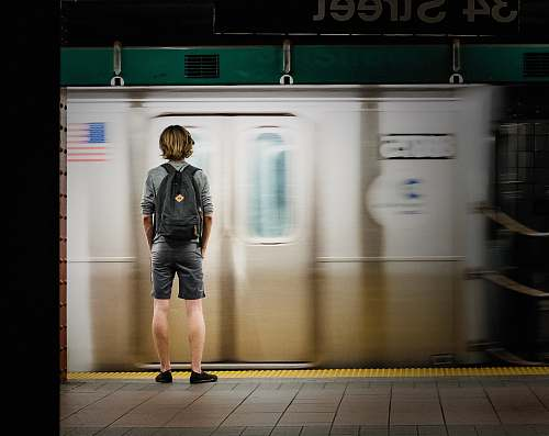 people time lapse photography of man standing in front of train person
