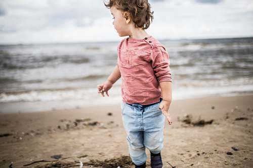people toddler boy standing on seashore person