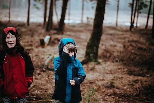 people two children wearing blue and red coats standing on woods person