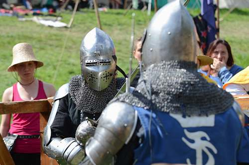 people two men wearing silver armor facing each other person