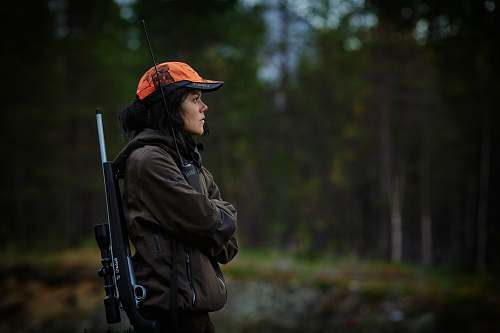 people woman carrying hunting rifle in woods person