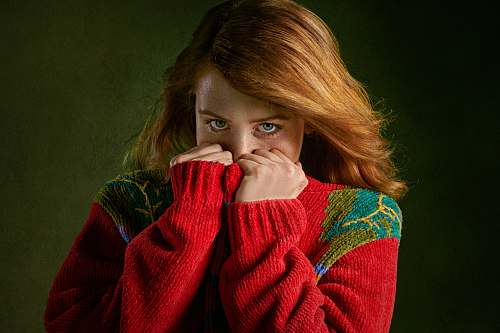 people woman covering mouth with sweater person