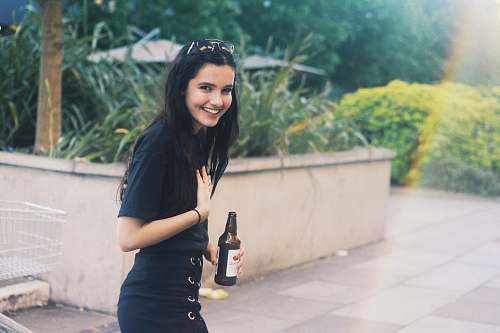 person woman holding black bottle in rule of thirds photography people