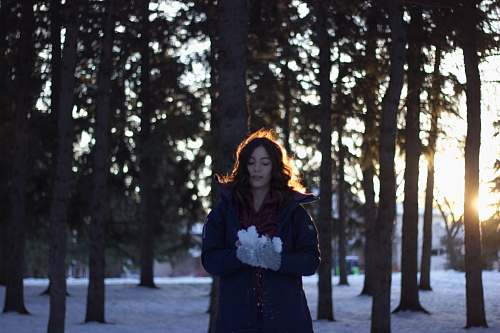 people woman holding snow near trees during sunset person