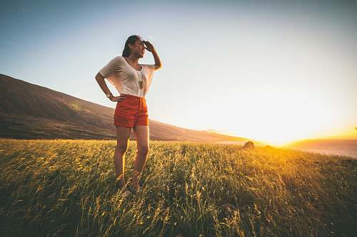people woman in beige batwing sleeved shirt and red shorts standing on grass field person