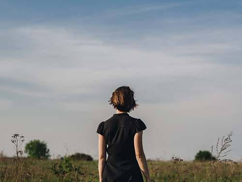 people woman in black shirt standing in grass field person