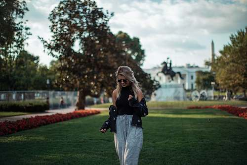 people woman in black top and white pants standing on green grass during daytime person