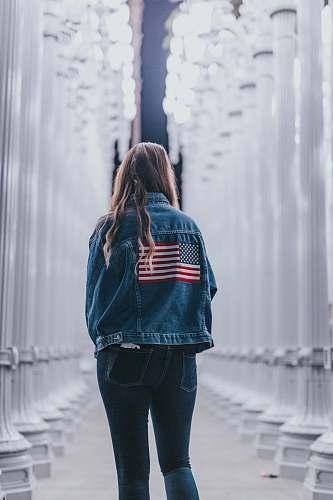 people woman in blue denim jacket standing near pedestals person