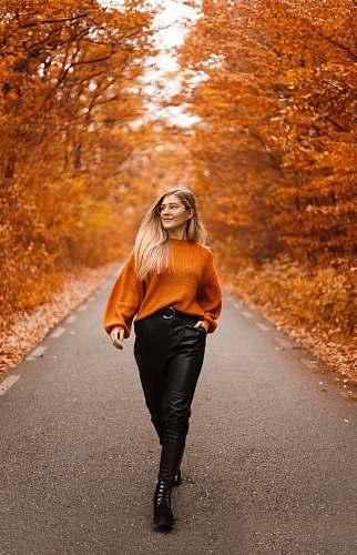people woman in orange sweater and black pants walking on street between orange trees person