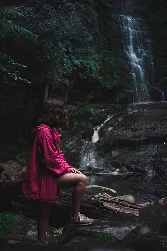 people woman in purple jacket standing near waterfalls person