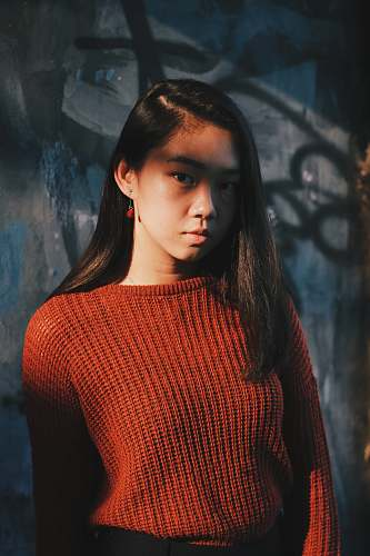 person woman in red sweater posing near gray wall people